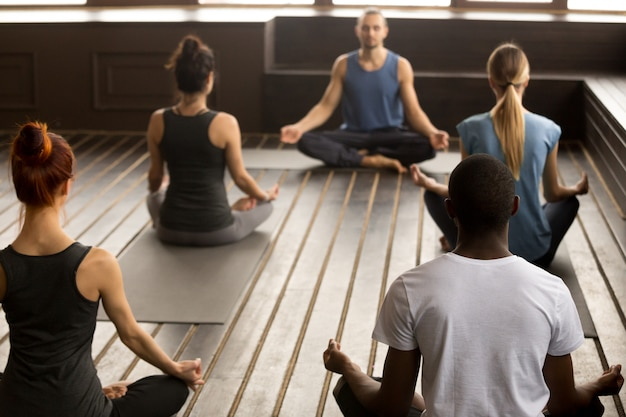 Grupo de jóvenes deportistas sentados en el ejercicio de sukhasana