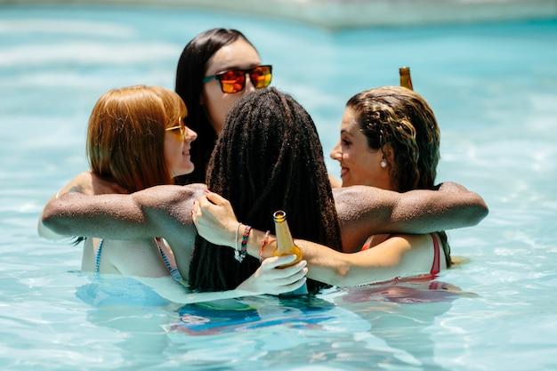 Grupo de jóvenes de diferentes etnias en una piscina abrazándose en un círculo con cervezas