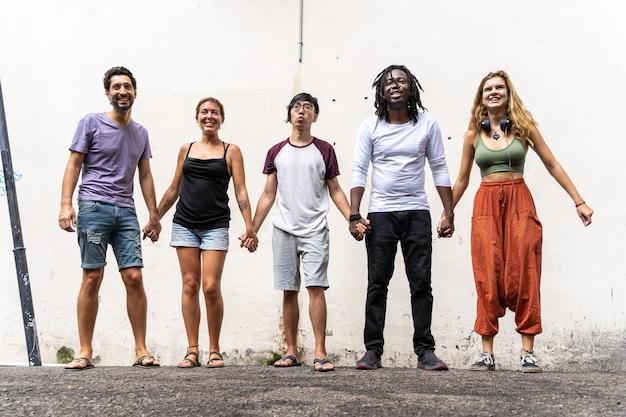 Grupo de jóvenes de diferentes grupos étnicos tomados de la mano junto a una pared.
