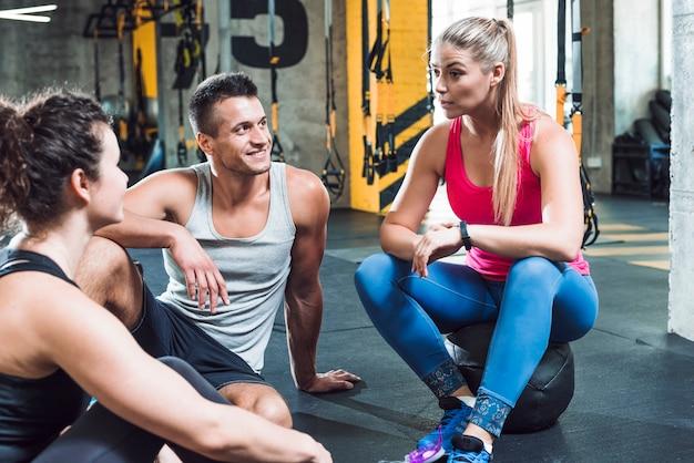 Grupo de jóvenes discutiendo en el gimnasio