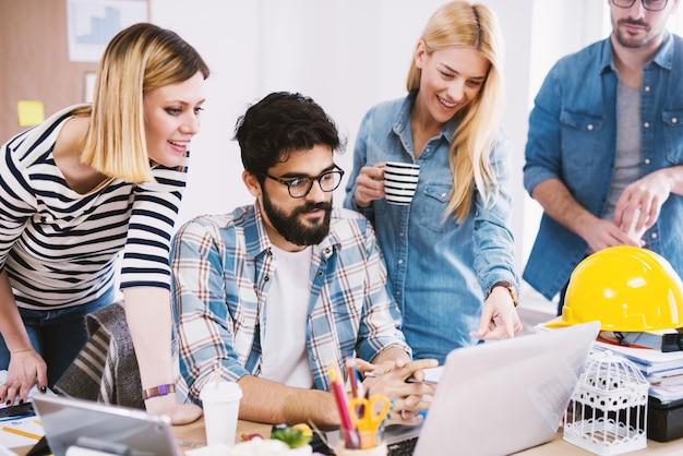 Grupo de jóvenes diseñadores innovadores enfocados que consultan en el escritorio de la oficina