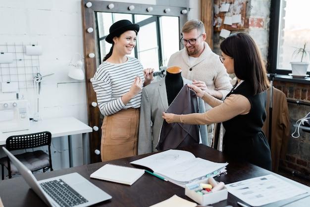 Grupo de jóvenes diseñadores de moda alegres de pie junto a maniquí mientras se discute la chaqueta sin terminar y el textil en el taller