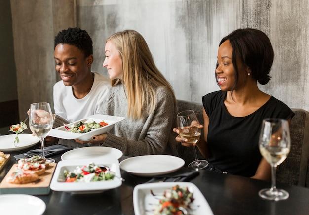 Grupo de jóvenes disfrutando de una cena y vino.