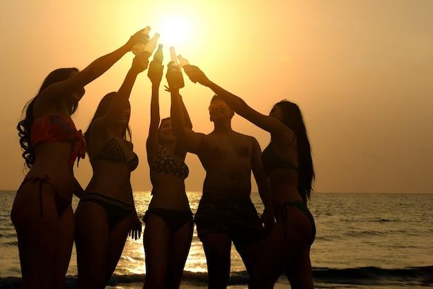 Grupo de jóvenes divirtiéndose bebiendo y bailando fiesta en la playa en vacaciones de verano crepúsculo puesta de sol