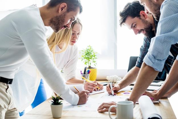 Grupo de jóvenes empresarios analizando gráfico sobre escritorio de madera