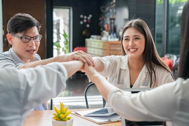 Grupo de jóvenes empresarios asiáticos que trabajan y unen sus manos en la oficina en casa, concepto de trabajo en equipo empresarial