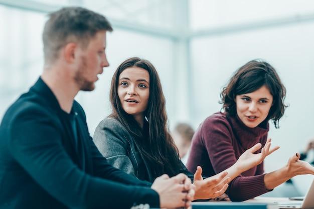 Grupo de jóvenes empresarios discutiendo información en línea