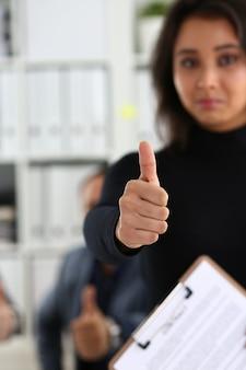 Grupo de jóvenes empresarios están felices de hacer un buen trato mostrar dedo grande