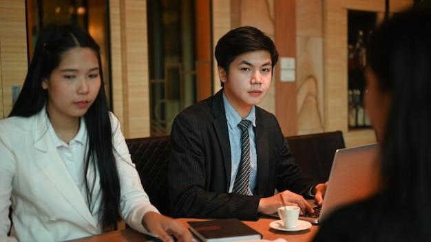 Grupo de jóvenes empresarios intercambiando ideas y discutiendo el plan de negocios en la sala de reuniones.