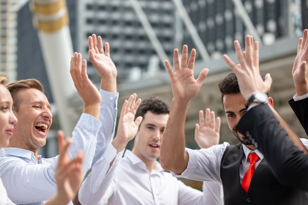 Grupo de jóvenes empresarios levantan la mano para lograr el objetivo