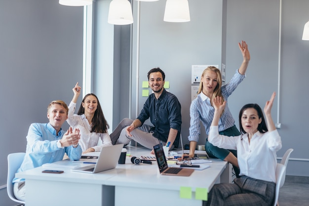 Grupo de jóvenes empresarios en una mesa agitando sus manos alegremente mientras miran a la cámara