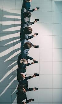 Grupo de jóvenes empresarios mirando las pantallas de sus teléfonos inteligentes