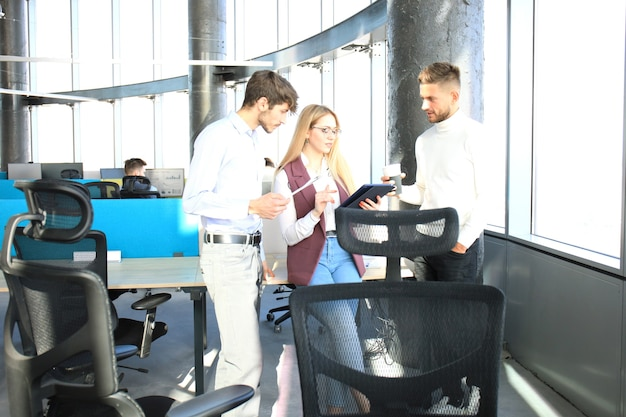 Grupo de jóvenes empresarios que trabajan y se comunican juntos en la oficina creativa.