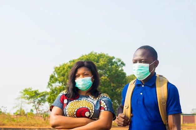 Grupo de jóvenes estudiantes africanos negros con mascarilla practicando el distanciamiento social