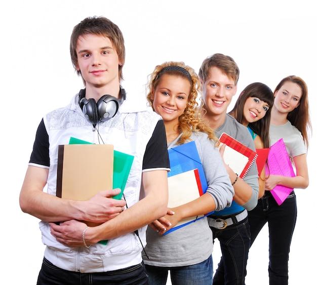 Grupo de jóvenes estudiantes alegres de pie con libros y bolsas