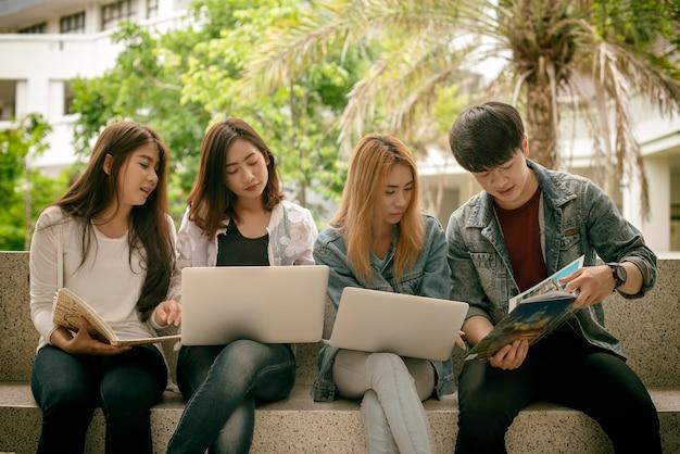 Grupo de jóvenes estudiantes con libros y cuadernos de trabajo informe de grupo se sientan en la mesa