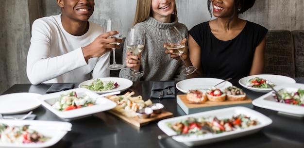 Grupo de jóvenes felices cenando y vino