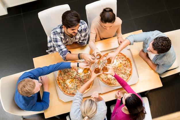 Grupo de jóvenes felices comiendo pizza y bebiendo sidra en el interior moderno