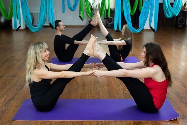 Grupo de jóvenes hacen yoga en el gimnasio sobre colchonetas, ejercicios de estiramiento y relajación. en forma y bienestar.
