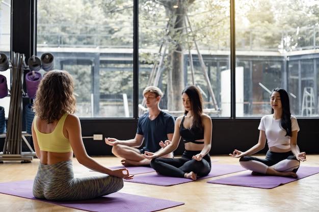 Grupo de jóvenes haciendo yoga sobre una estera de yoga con un entrenador gradualmente enseñando.
