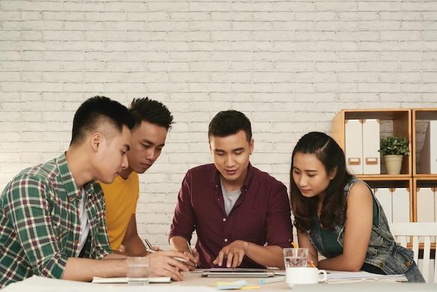 Grupo de jóvenes hombres y mujeres asiáticos de pie juntos alrededor de la mesa y mirando la tableta