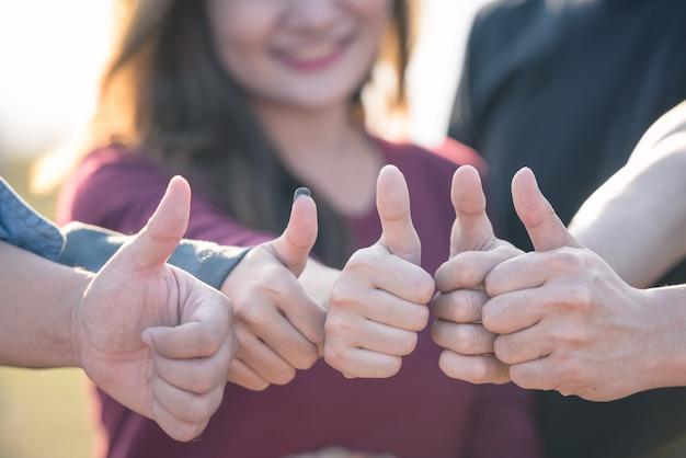 Grupo de jóvenes manos con los pulgares hacia arriba juntos expresando positividad, conceptos de trabajo en equipo.