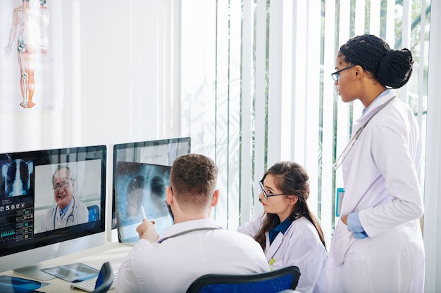 Grupo de jóvenes médicos discutiendo radiografía de pulmones de paciente recuperado de coronavirus