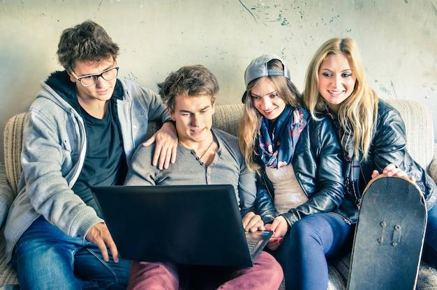 Grupo de jóvenes mejores amigos hipster con computadora en estudio alternativo urbano