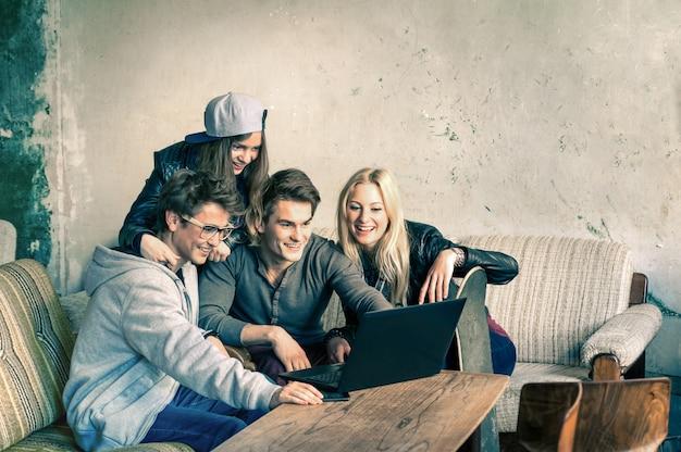 Grupo de jóvenes mejores amigos hipster con computadora portátil en ubicación alternativa urbana