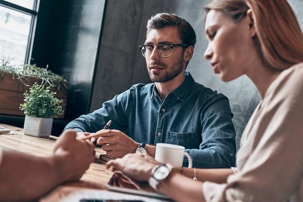 Grupo de jóvenes modernos en ropa casual elegante discutiendo algo mientras trabaja en la oficina