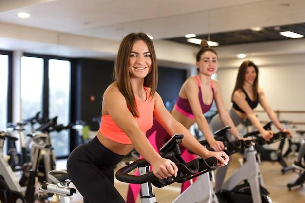 Grupo de jóvenes mujeres delgadas de entrenamiento en bicicleta estática en el gimnasio. concepto de estilo de vida deportivo y de bienestar