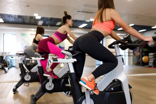 Grupo de jóvenes mujeres delgadas de entrenamiento en bicicleta estática en el gimnasio, el deporte y el concepto de estilo de vida de bienestar
