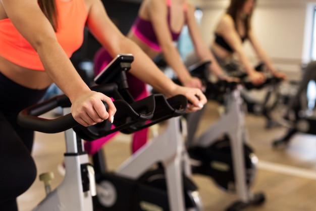 Grupo de jóvenes mujeres delgadas de entrenamiento en bicicleta estática en el gimnasio.