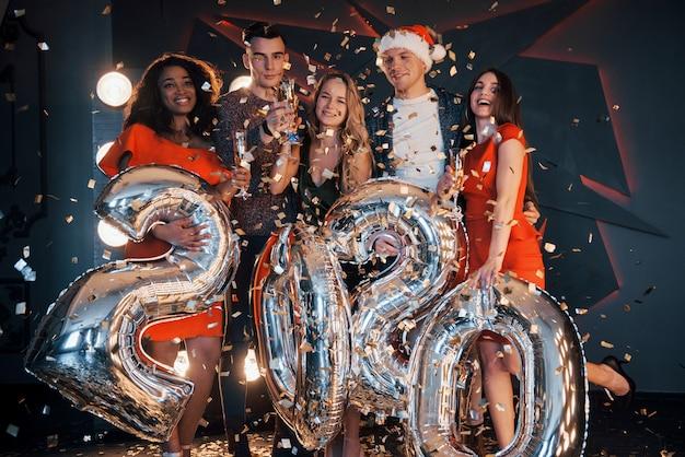 Un grupo de jóvenes multinacionales hermosas y divertidas lanzando confeti en una fiesta. celebración de 2020.