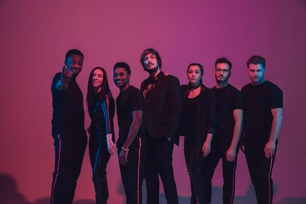 Grupo de jóvenes músicos multiétnicos creó banda, bailando en luz de neón sobre fondo rosa. concepto de música, afición, festival, bienestar. anfitrión de fiesta alegre, bailarín, cantante, guitarrista, saxofonista.
