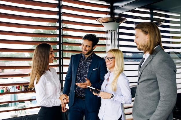 Grupo de jóvenes en la oficina moderna tiene reunión de equipo y lluvia de ideas