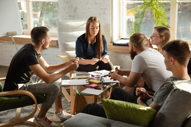 Grupo de jóvenes oficinistas caucásicos reunidos para discutir nuevas ideas