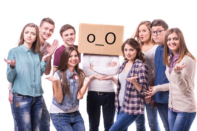 Grupo de jóvenes de pie con la caja de la cabeza.