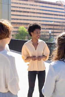 Grupo de jóvenes de pie en la calle y hablando