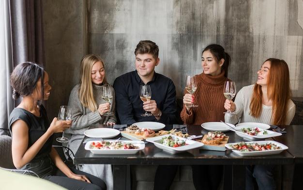 Grupo de jóvenes positivos disfrutando de una cena y vino.