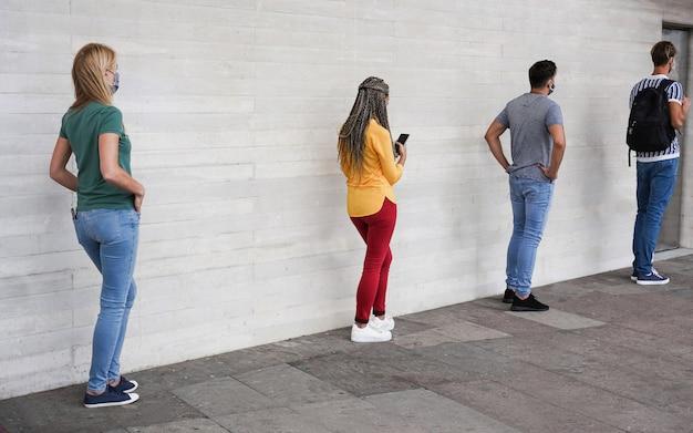 Grupo de jóvenes que esperan entrar en un mercado de tiendas mientras mantienen la distancia social en una línea durante el tiempo del coronavirus