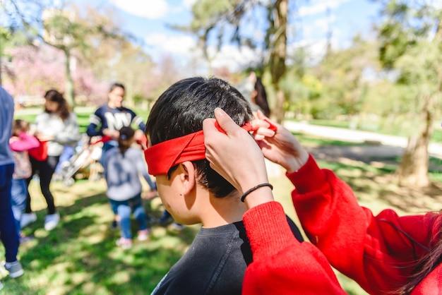 Grupo de jóvenes que juegan en una escuela al aire libre se cubren los ojos con un velo rojo para encontrar al compañero