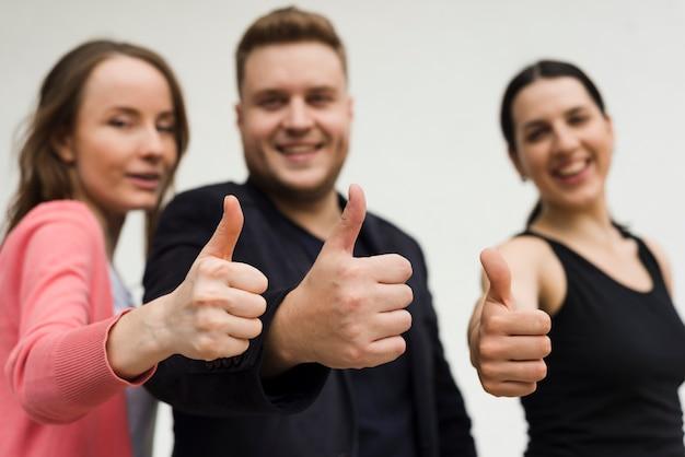 Grupo de jóvenes que muestran gesto de pulgar hacia arriba