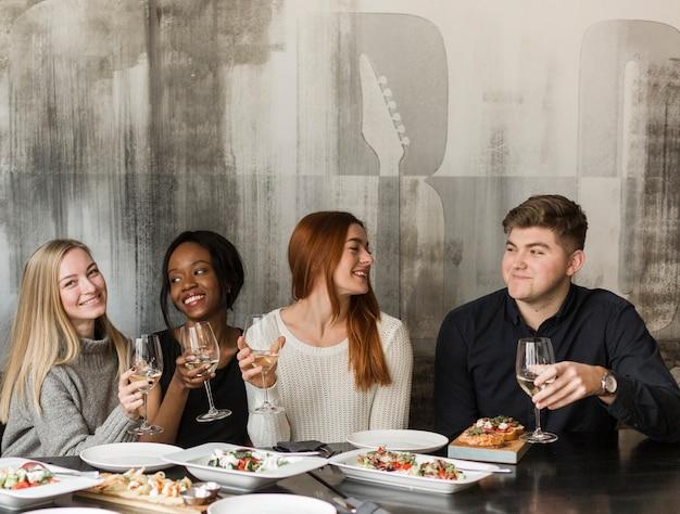 Grupo de jóvenes reunidos para cenar