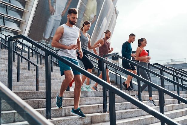 Grupo de jóvenes en ropa deportiva para correr mientras hace ejercicio en las escaleras al aire libre