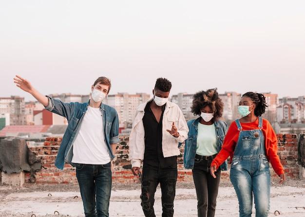 Grupo de jóvenes saliendo con mascarillas quirúrgicas