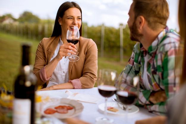 Grupo de jóvenes sentados a la mesa y bebiendo vino tinto en el viñedo