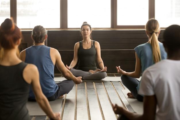 Grupo de jóvenes sentados en sukhasana