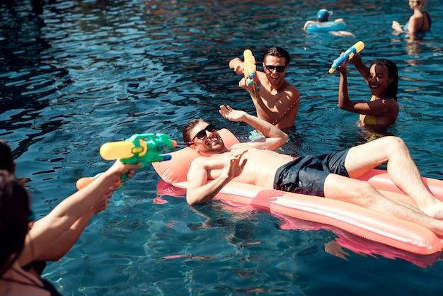 Grupo de jóvenes sonrientes amigos divirtiéndose en la piscina