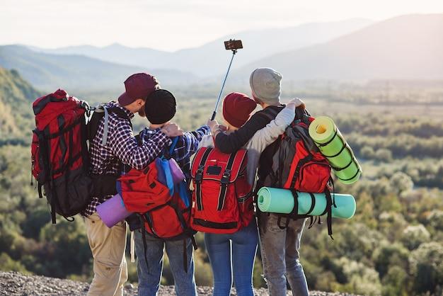 Grupo de jóvenes sonrientes que viajan juntos en las montañas.